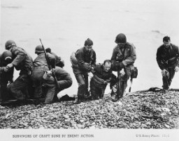 "<p>US troops pull the survivors of a sunken craft on to the shores of the Normandy beaches on <a href=""/narrative/2899/en"">D-Day</a>. Normandy, France, June 6, 1944.</p>"