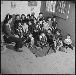 """<p>A group of nursery school children at the Heart Mountain Relocation Center in Wyoming, January 4, 1943. The Heart Mountain Relocation Center was one of ten <a href=""""/narrative/32232"""">relocation centers</a> where Japanese Americans were forcibly deported.</p>"""
