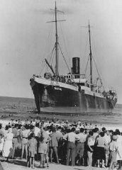 "<p>Aliyah Bet (""illegal"" immigration) ship <em>Tiger Hill</em>, carrying Jewish refugees from Europe, lands in Tel Aviv, Palestine. Jewish residents of Palestine greet the ship. September 1, 1939.</p>"
