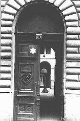 <p>Entrance to the courtyard, marked with a Star of David, of a building designated for Jews. Budapest, Hungary, after April 2, 1944.</p>