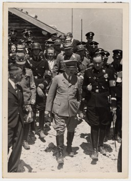 Adolf Hitler walks and converses in a group with other Nazis