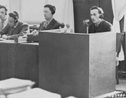 "<p>A Polish former inmate of <a href=""/narrative/3673/en"">Auschwitz</a> identifies Oswald Pohl while on the stand for the prosecution during the <a href=""/narrative/9488/en"">Pohl</a>/WVHA trial. This trial, case #4 of the <a href=""/narrative/9461/en"">Subsequent Nuremberg Proceedings</a>, took place in a room in the Palace of Justice which was not the main courtroom. Nuremberg, Germany, April 18, 1947.</p>"