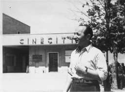 "<p>Edward Arzt, a Jewish <a href=""/narrative/5232/en"">displaced person</a> (DP), stands at the entrance to the <a href=""/narrative/53718/en"">Cinecittà</a> DP camp in Rome, Italy, 1947. Arzt and his family lived in the camp for three years before immigrating to the United States.</p>"