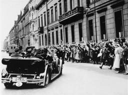 <p>Cheering spectators greet Hitler upon his departure for the Reichstag session at which the Enabling Act was passed. The act allowed the government to issue laws without the consent of Germany's parliament, laying the foundation for the complete Nazification of German society.</p>