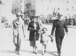 "<p>A Jewish family strolls along a street in prewar <a href=""/narrative/7584/en"">Kalisz</a>. Poland, May 16, 1935.</p>"