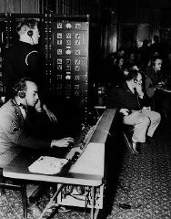 <p>İngilizce, Fransızca, Rusça ve Almanca Nuremberg mahkemelerindeki resmî dillerdi. Çevirmenler davaların simültane çevirisini yaptı. Burada mahkemeye katılanlar santral yoluyla çevirileri dinliyor. Kasım 1945, Nuremberg, Almanya.</p>