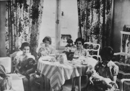 Anne Frank, Ellen Weinberger, Margot Frank and Gabrielle Kahn having a tea party with their dolls at the home of Gabrielle Kahn in Amsterdam, Netherlands, 1934