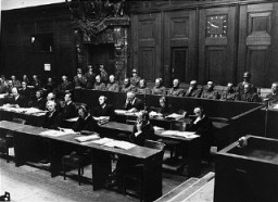 """<p>The defendants in the dock (at rear, with headphones) and their lawyers (front) follow the proceedings of the <a href=""""/narrative/9521"""">Hostage Case</a>, case #7 of the <a href=""""/narrative/9461"""">Subsequent Nuremberg Proceedings</a>. Nuremberg, Germany, 1947-48.</p>"""