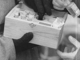 <p>Sovyet askerleri içinde tıbbî deneylerde kullanılan zehir olan bir kutuyu inceliyor. 27 Ocak 1945'ten sonra, Auschwitz, Polonya.</p>