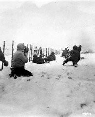 <p>John Perry, photographe de cinéma au sein de l'unité 129, filme des GI du 290e régiment d'infanterie, de la 75e division d'infanterie et du groupe de la 4e cavalerie à la recherche de snipers allemands, près de Beffe, en Belgique, début janvier 1945. Douze Allemands furent tués ce jour-là. La scène a été photographiée par Carmen Corrado de la 129e unité. 7 janvier 1945. Corps de transmission de l'Armée américaine, photographie prise par C.A. Corrado.</p>