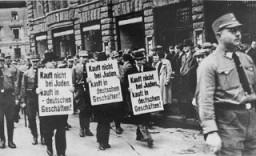 <p>標識を手に、混み合うライプツィヒの路上を強制的に行進させられる3人のユダヤ人実業家。標識には 「ユダヤ人から買うな!ドイツ人の店で買え!」と書かれている。1935年、ドイツ、ライプツィヒ。</p>