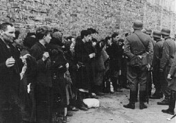 """<p class=""""document-desc moreless"""">Jews captured by the SS during the <a href=""""/narrative/3636/en"""">Warsaw ghetto uprising</a> are interrogated beside the ghetto wall before being sent to the Umschlagplatz, the assembly point for <a href=""""/narrative/5199/en"""">deportation</a> from the ghetto. The original German caption reads: """"Search and Interrogation.""""Poland, May 1943.</p>"""