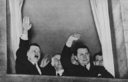 <p>Adolf Hitler, Wilhelm Frick, and Hermann Göring wave to a torchlight parade in honor of Hitler's appointment as chancellor. Behind Göring stands Rudolf Hess. Berlin, Germany, January 30, 1933.</p>