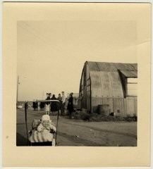 "<p>A young baby sits in its carriage next to a Quonset hut in <a href=""/narrative/11669/en"">Babenhausen displaced persons camp</a>. Babenhausen, Germany, 1946-47.</p>"