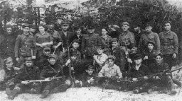 Group portrait of members of the Kalinin Jewish partisan unit (Bielski group) on guard duty at an airstrip in the Naliboki Forest. [LCID: 46677]
