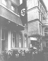 <p>Advogados judeus em fila para solicitar uma permissão para comparecer perante a corte de Berlim. Novas regras estabelecidas no Parágrafo Ariano (uma série de leis decretadas em abril de 1933 que proibiam a participação de judeus em várias esferas públicas e sociais) permitiam que somente 35 deles comparecessem perante a corte. Berlim, Alemanha, 11 de abril de 1933.</p>