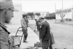 <p>As a German soldier looks on, Tunisian Jews are forced to sweep the street and move a wooden crate on a hand cart. Tunisia, 1942-43.</p>