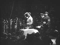 <p>In this German newsreel footage, Hitler addresses members of the SA and the SS in the Sportpalast, a sports arena in Berlin, Germany. He thanks them for their support and sacrifice during the Nazi struggle for power.</p>