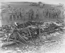 <p>While on an inspection tour of the newly liberated Ohrdruf concentration camp, American soldiers view the charred remains of prisoners burned upon a section of railroad track during the evacuation of the camp. Ohrdruf, Germany, April 4-15, 1945.</p>