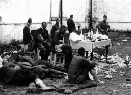 """<p>Wounded <a href=""""/narrative/10135/en"""">Soviet prisoners of war</a>await medical attention. The German army provided only minimal treatment, and permitted captured Soviet personnel to care for their own wounded using only captured medical supplies. Baranovichi, Poland, wartime.</p>"""