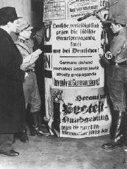 "<p>Members of the SA post signs demanding that Germans boycott <a href=""/narrative/102/en"">Jewish-owned businesses</a>. Berlin, Germany, April 1, 1933.</p>"