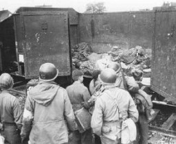 <p>US soldiers discovered these boxcars loaded with dead prisoners outside the Dachau camp. Here, they force German boys—believed to be members of the Hitler Youth (Hitlerjugend; HJ)—to view the atrocity. Dachau, Germany, April 30, 1945.</p>