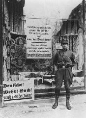 <p>During the anti-Jewish boycott, an SA man stands outside a Jewish-owned store with a sign demanding that Germans not buy from Jews. Berlin, Germany, April 1, 1933.</p>