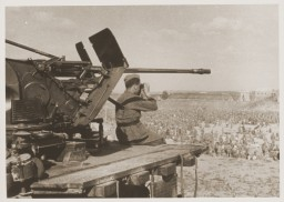 "<p>A German guard sitting on the end of a 20mm gun platform watches over 50,000 <a href=""/narrative/10143/en"">Soviet Prisoners of War</a> (POWs) at Stalag 349, Ukraine, August 14, 1941.</p>"
