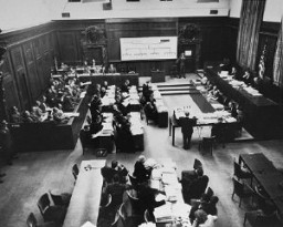 """<p>The courtroom during the <a href=""""/narrative/9545"""">Einsatzgruppen Trial</a> of the Subsequent Nuremberg Proceedings. Chief Prosecutor Benjamin Ferencz stands in the center of the room. He is presenting evidence. Nuremberg, Germany, between September 29, 1947, and April 10, 1948.</p>"""