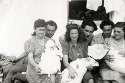 "<p>Three couples pose with their babies in the <a href=""/narrative/53809/en"">Gabersee</a> displaced persons (DP) camp in Germany, 1947. In the center are David and Bella Perl (later spelled Pearl), who met and married after the war, with their daughter, Rachel.</p>