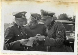 """<p>Richard Baer and Karl Höcker look over a document with SS-Standartenführer Dr. Enno Lolling, the director of the Office for Sanitation and Hygiene in the Inspectorate of Concentration Camps. From left to right: Lolling, Baer, Höcker.</p> <p><span style=""""font-weight: 400;"""">From <a href=""""/narrative/10865/en"""">Karl Höcker's photograph album</a>, which includes both documentation of official visits and ceremonies at Auschwitz as well as more personal photographs depicting the many social activities that he and other members of the Auschwitz camp staff enjoyed. These rare images show Nazis singing, hunting, and even trimming a Christmas tree. They provide a chilling contrast to the photographs of thousands of Hungarian Jews deported to Auschwitz at the same time. </span></p>"""