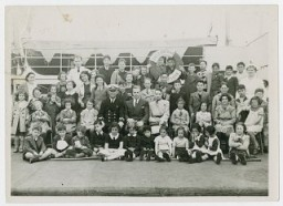 "<p>Gilbert and Eleanor Kraus (seated in the center, next to the ship's caption ) pose with the fifty Austrian Jewish children they brought to the <a href=""/narrative/3486/en"">United States</a>. Photograph taken in June 1939.</p>