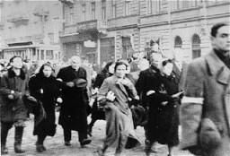 <p>يهود من الحي اليهودي في وارصوفيا يجبَرون على السير في مسيرة في الحي اليهودي أثناء الترحيل. وارصوفيا، بولندا، عام 1942-1943.</p>