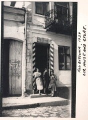 "<p><a href=""/narrative/10265/en"">Norman</a>'s sisters Malcia, Matla, and Rachel eat bagels in the doorway of their mother's store. The red and white stripes on the door frames indicate that the store carried cigarettes, matches, and sugar, consumer goods regulated by a state monopoly. Kolbuszowa, Poland, 1934.</p>