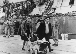 "<p>Refugees who were removed from the <a href=""/narrative/5265""><em>Exodus 1947</em></a> refugee ship walk to another ship which will return them to Europe. Haifa, Palestine, July 1947.</p>"