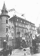 <p>German citizens stand outside the decorated Hotel Dreesen, where Neville Chamberlain and Hitler held their second meeting on the Sudetenland and German demands for Czech territory.  Nazi flags and the Union Jack fly from the building. Bad Godesberg, Germany, September 22, 1938.</p>