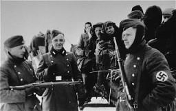 <p>Jeunes soldats allemands assistant à la déportation des Juifs du ghetto de Zychlin vers le camp de Chelmno. Les nazis avaient préparé la déportation pour qu'elle ait lieu lors de la fête juive de Pourim. Pologne, 3 mars 1942.</p>