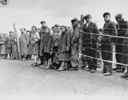 """<p>Soon after <a href=""""/narrative/8176/en"""">liberation</a>, camp survivors wait for rations of potato soup. Bergen-Belsen, Germany, April 28, 1945.</p>"""