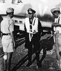 "<p><a href=""/narrative/12005/en"">Erwin Rommel</a> (center), German commander of the Africa Corps, at an airfield in Libya during an Axis offensive into neighboring Egypt. British troops decisively defeated Rommel's forces at El Alamein. Libya, September 8, 1942.</p>"