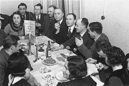"<p>Members of the Chug Ivri (Hebrew Club) in Berlin enjoy a festive meal in celebration of <a href=""/narrative/9164/en"">Purim</a>. Berlin, Germany, 1935.</p>"