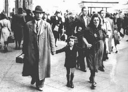 "<p>Members of a Jewish family walking along a Berlin street wear the compulsory Star of David <a href=""/narrative/11750"">badge</a>. Berlin, Germany, September 27, 1941.</p>"