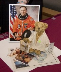 "<p>A replica of ""Refugee"" bear and a photo of a Darfurian child refugee, items taken by Commander Mark Polansky (pictured) on a December 2006 Space Shuttle mission.</p>"