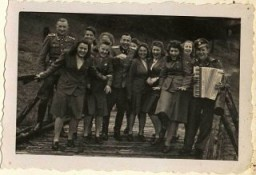 """<p>SS female auxiliaries (Helferinnen) run down a ramp in Solahütte to the music of an accordion.</p> <p><span style=""""font-weight: 400;"""">From <a href=""""/narrative/10865/en"""">Karl Höcker's photograph album</a>, which includes both documentation of official visits and ceremonies at Auschwitz as well as more personal photographs depicting the many social activities that he and other members of the Auschwitz camp staff enjoyed. These rare images show Nazis singing, hunting, and even trimming a Christmas tree. They provide a chilling contrast to the photographs of thousands of Hungarian Jews deported to Auschwitz at the same time. </span></p>"""