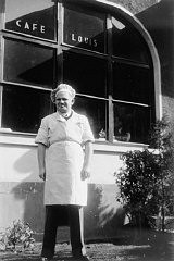 """<p>German Jewish <a href=""""/narrative/2419/en"""">refugee</a> Erwin Eisfelder stands outside Cafe Louis on Ward Road. The cafe was named in honor of his father. It was a popular gathering place for refugees in Shanghai during the war years. Shanghai, China, ca. 1944.</p>"""