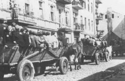 """<p>Juifs, pour la plupart enfants, avançant sur des voitures tirées par des chevaux vers les points de rassemblement pour être déportés. Ils sont gardés par la police juive. Ghetto de Lodz, Pologne, au cours de l'action """"Gehsperre"""" (action couvre feu), du 5 au 12 septembre 1942.</p>"""