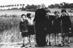 "<p><a href=""/narrative/11649"">Father Bruno</a> with Jewish children he hid from the Germans. Yad Vashem recognized Father Bruno as ""Righteous Among the Nations."" Belgium, wartime.</p>"