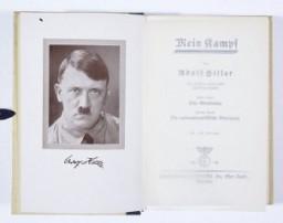 """<p>الصفحة الأولى لكتاب """"كفاحي"""" لأدولف هتلر. هذه النسخة لديها نقش من قبل هتلر على الغلاف الداخلي (لا يظهر): """"للعروسين مع أطيب التمنيات لزواج سعيد ومبارك"""". ميونيخ ، ألمانيا، 1941 .</p>"""