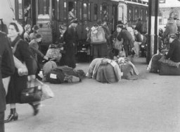 "<p>Scene during the deportation of German Jews to <a href=""/narrative/5386/en"">Theresienstadt</a> ghetto. Jewish deportees from the Hanau, Gelnhausen and Schluechtern districts wait with their luggage on the platform at the Hanau station before boarding the deportation train. Hanau, Germany, May 30, 1942.</p>"
