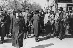 """<p>Dos hombres judíos (en el centro y a la derecha, con un abrigo) transportando pintura y pinceles; eran obligados por los nazis austríacos a pintar """"Jude"""" (""""judío"""" en alemán) en el frente de los comercios de propiedad judía. Viena, Austria, 1938.</p>"""