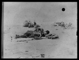<p>Armenian refugees in the desert. A man in the foreground lies on the ground on a layer of bedding. 1915-20.</p>